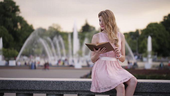 Devojka koja čita knjigu pored fontane
