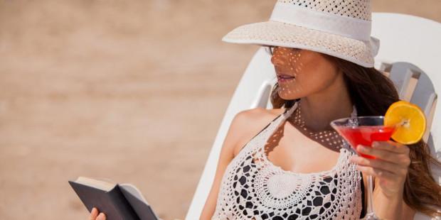 Devojka čita knjigu na plaži dok pije koktel